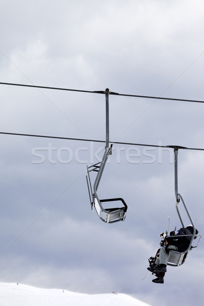 Snowboarders in chair lift at gray windy day Stock photo © BSANI