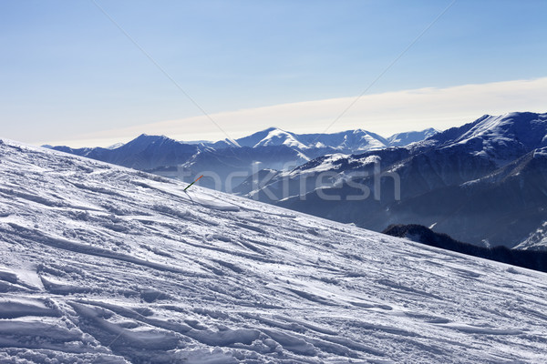 Ski slope with trace of ski, snowboards and mountains in haze Stock photo © BSANI