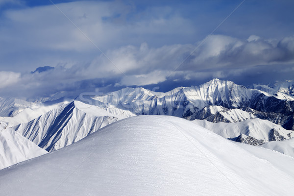 Top of off-piste snowy slope and cloudy mountains Stock photo © BSANI