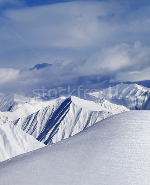 Top of off-piste snowy slope and cloud mountains Stock photo © BSANI
