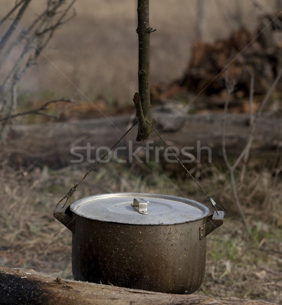 Cooking in old sooty cauldron on campfire Stock photo © BSANI