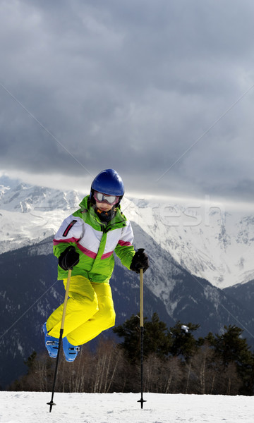 Young skier jump with ski poles in sun winter mountains Stock photo © BSANI