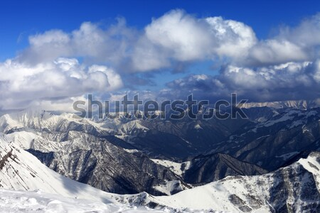Sunlit winter mountains in clouds, view from off-piste slope Stock photo © BSANI