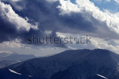 Helicopter in winter mountains and cloudy sky in evening Stock photo © BSANI
