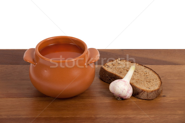 Borsch in ceramic pot with bread and garlic on wooden table Stock photo © BSANI