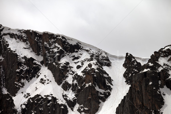 Rocks with snow cornice in gray day Stock photo © BSANI