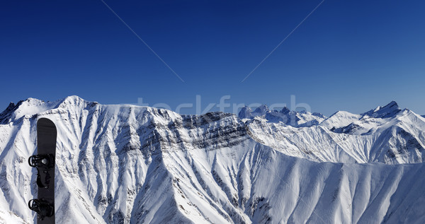 Panoramic view on snowy mountains and snowboard Stock photo © BSANI