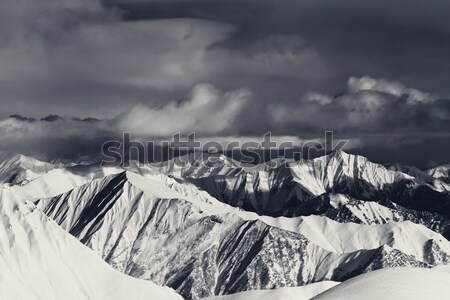 Black and white snowy mountains in clouds and off-piste slope Stock photo © BSANI