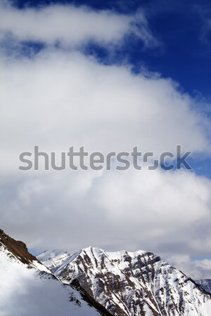 Winter snowy mountains and sky with clouds at sun day Stock photo © BSANI