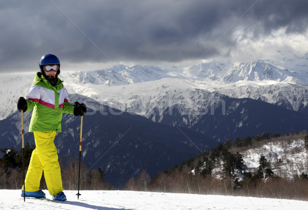 Young skier with ski poles in sun mountains and cloudy gray sky Stock photo © BSANI
