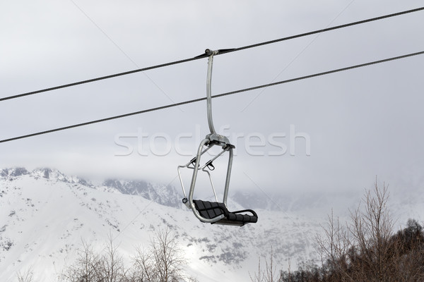 Chair lift and snowy mountains in haze Stock photo © BSANI
