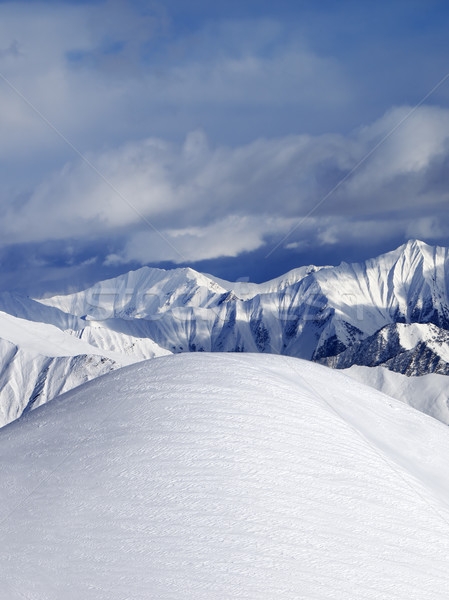 Top of off piste snowy slope and cloudy mountains Stock photo © BSANI