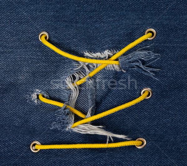 Blue jean with hole and crisscross lacing Stock photo © BSANI