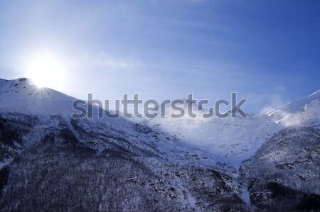 Snowy mountains in haze and sky with sun, view from off piste sl Stock photo © BSANI