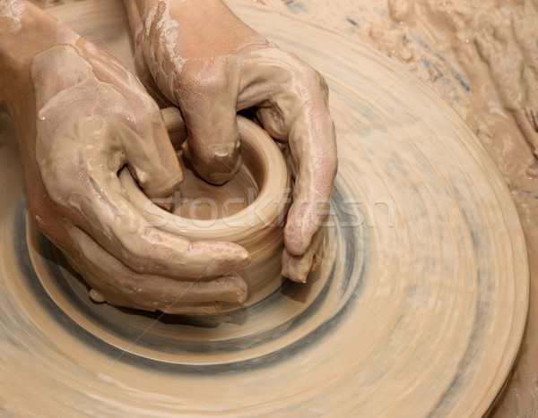 Hands in clay at process of making ceramic on pottery wheel Stock photo © BSANI