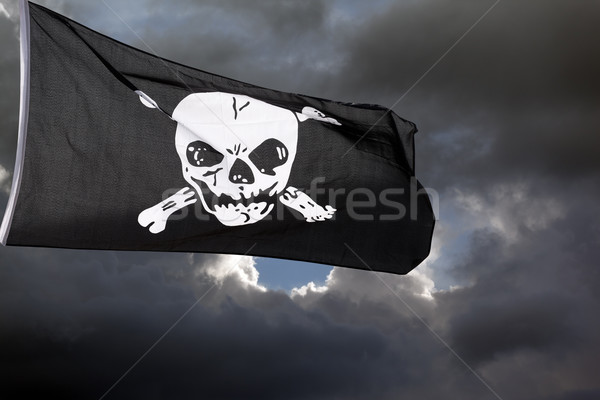 Jolly Roger (pirate flag) against storm clouds Stock photo © BSANI