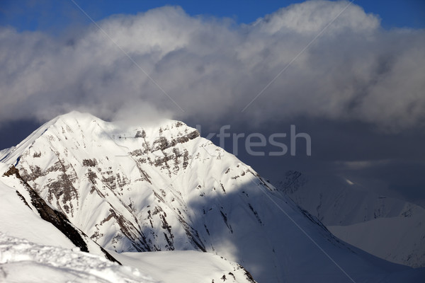 Snowy sunlit mountains and blue sky with clouds Stock photo © BSANI