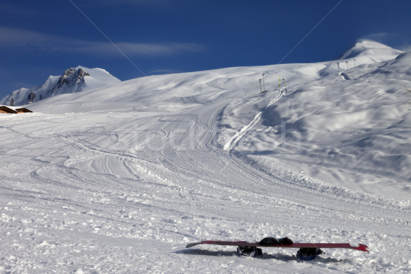 Snowboard in snow on ski slope at sun windy evening Stock photo © BSANI