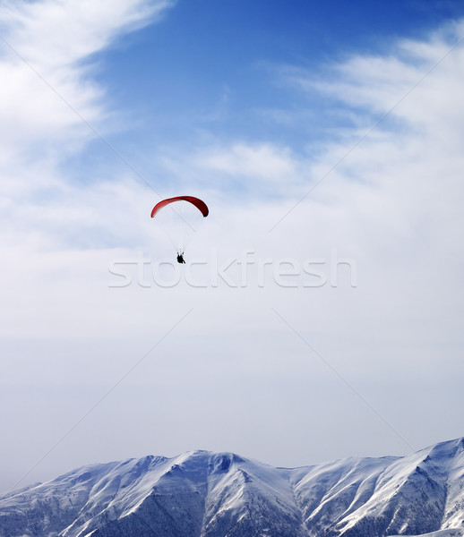 Paraglider silhouette of mountains in windy sky at sun day Stock photo © BSANI