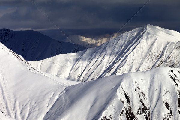 Stock photo: Snowy sunlit mountains and overcast sky