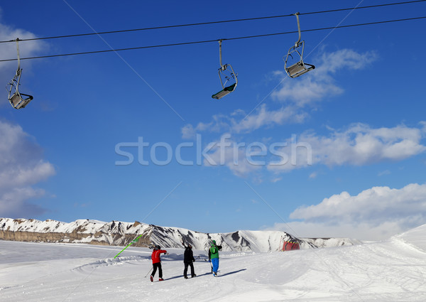 Stock photo: Three skiers on slope at sun nice day