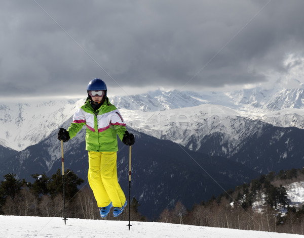 Young skier jumping with ski poles in sun mountains and cloudy g Stock photo © BSANI