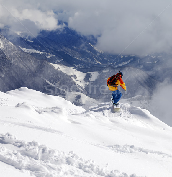 Stock photo: Snowboarder on off-piste slope an mountains in haze