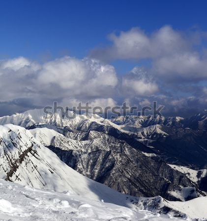 Snowy rocks in clouds at sunny day Stock photo © BSANI