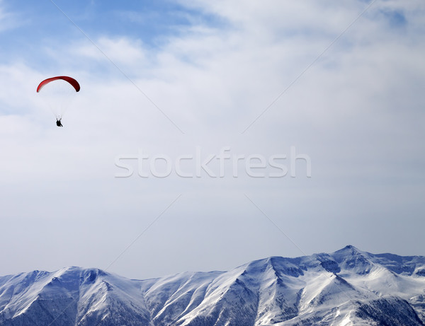 Paraglider silhouette of mountains in sunlight sky Stock photo © BSANI
