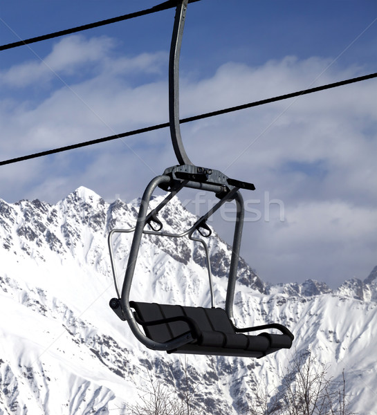 Stock photo: Chair lift in snowy mountains at nice sun day
