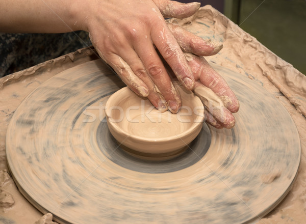 Woman hands in clay at process of making clay bowl on pottery wh Stock photo © BSANI