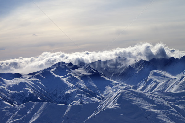 Snowy mountains in mist at winter evening Stock photo © BSANI