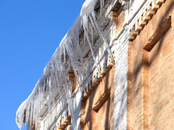 Snow-covered roof of old house with icicles Stock photo © BSANI