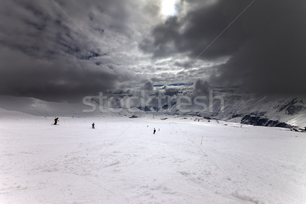 Ski slope, skiers and sky with storm clouds Stock photo © BSANI