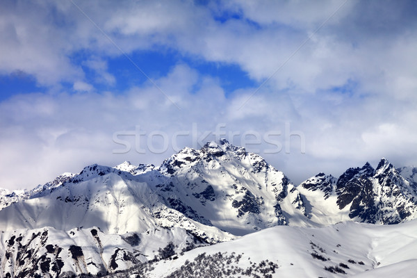 Snow slope and winter sunlight mountains in clouds Stock photo © BSANI