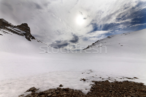 Snowy mountain pass and sky with clouds at evening Stock photo © BSANI