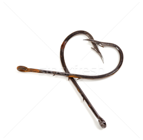 Old fish hooks in form of heart on white Stock photo © BSANI
