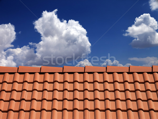 Roof tiles against blue sky with clouds Stock photo © BSANI