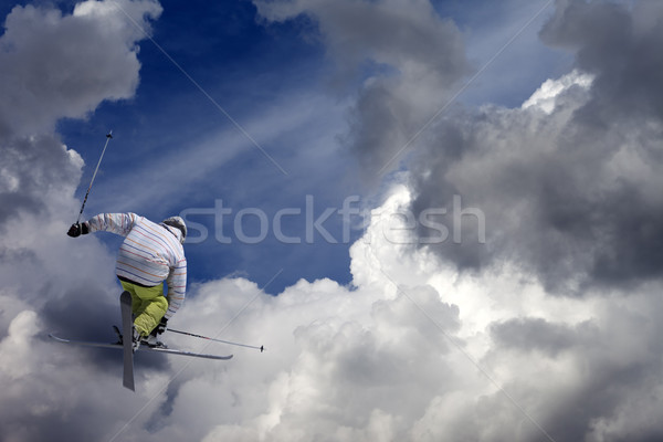 Freestyle ski jumper with crossed skis against blue sky with clo Stock photo © BSANI