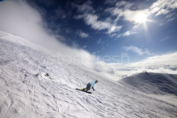 Snowboarder on off-piste ski slope and blue sky with sun Stock photo © BSANI