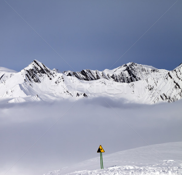 Mountains in mist and warning sing on off-piste slope Stock photo © BSANI