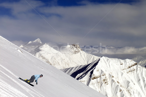 Snowboarder on off-piste slope in mountains Stock photo © BSANI