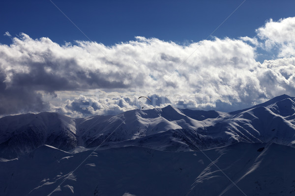 Stock photo: Evening sunlight mountain with clouds and silhouette of parachut