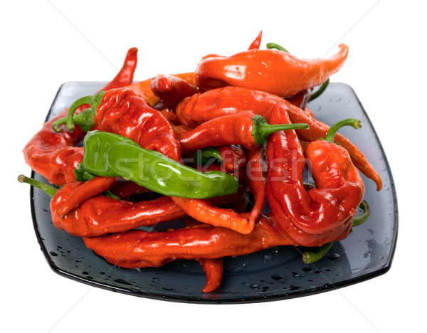 Red and green peppers on glass plate Stock photo © BSANI