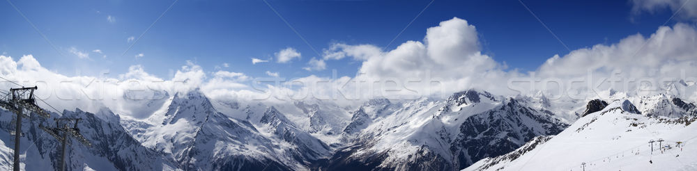 Panoramic view on ski slope and cloudy mountains at sun day Stock photo © BSANI