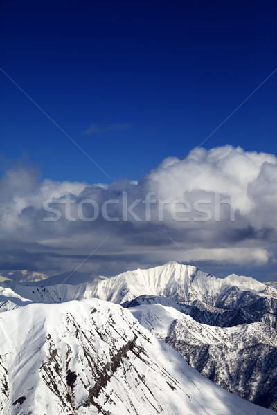 Winter snowy sunlit mountains and sky with clouds Stock photo © BSANI