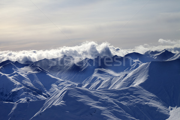 Evening snowy mountains in mist and sunlight clouds Stock photo © BSANI