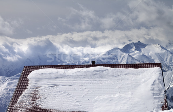 Snowy roof and mountains in clouds Stock photo © BSANI