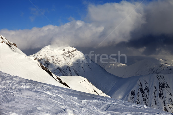 Off-piste slope and sunlit mountains in clouds Stock photo © BSANI