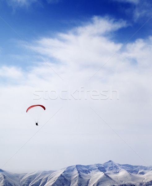 Parachutist silhouette of mountains in windy sky Stock photo © BSANI